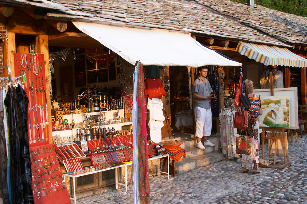 The busy old market bazaar street Kujundziluk with lots of tourist craft and art shops and street merchants. Shop selling jewelleries and brass things. Historic town of Mostar. Federation Bosne i Hercegovine. Bosnia Herzegovina, Europe.