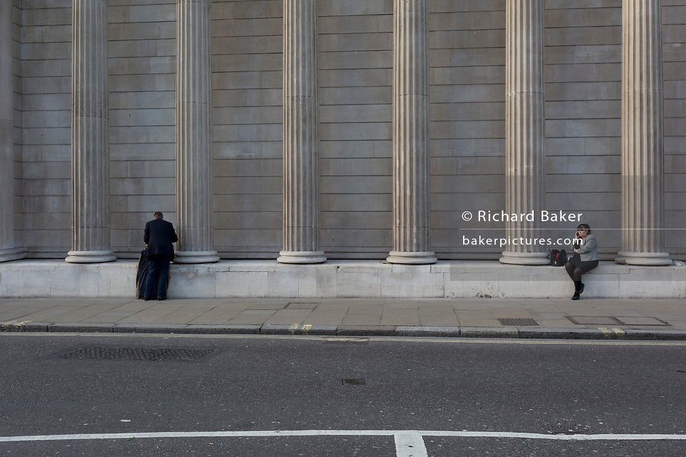 A lady checks for messages and uses social media beneath the walls of the Bank of England, on 30th October 2017, Threadneedle Street, in the City of London, England.