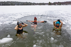Aviemore, Scotland, UK. 4 February 2021. Loch Vaa is completely frozen and offers opportunity to walk across it. A small boathouse is now icebound and three ladies from the InVaa Dookers wild swimming group use axes to break the ice to allow them to soak in the icy water for a few minutes. Pic; Carolyn Stead, Lorna Foster and Wendy Cathcart enjoy a dip in icy Loch Vaa.  Iain Masterton/Alamy Live News
