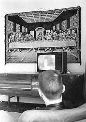 Young man sitting in lounge of Salvation Army hostel watching television,