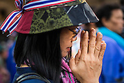 """15 JANUARY 2014 - BANGKOK, THAILAND: A Buddhist woman prays at the main protest site for Shutdown Bangkok. Tens of thousands of Thai anti-government protestors continued to block the streets of Bangkok Wednesday to shut down the Thai capitol. The protest, """"Shutdown Bangkok,"""" is expected to last at least a week. Shutdown Bangkok is organized by People's Democratic Reform Committee (PRDC). It's a continuation of protests that started in early November. There have been shootings almost every night at different protests sites around Bangkok. The malls in Bangkok are still open but many other businesses are closed and mass transit is swamped with both protestors and people who had to use mass transit because the roads were blocked.    PHOTO BY JACK KURTZ"""