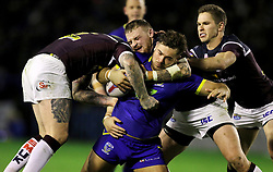 Warrington's Joe Philbin is tackled by Leeds Rhino's Brett Delaney and Adam Cuthbertson during the Betfred Super League match at the Halliwell Jones Stadium, Warrington.