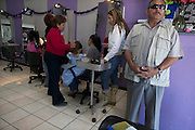 """José's daughter prepares to attend her """"princess"""" themed birthday party while one of her personal guards stands by on alert. The guard stood outside at first but then moved inside after seeing a suspicious person enter the outdoor restaurant next door."""