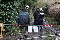Harefield, UK. 14 January, 2020. An activist looks on as enforcement agents working on behalf of HS2 liaise at the entrance to a public right of way leading to a protection camp from which Stop HS2 activists are currently being evicted before deciding to deny access to press. 108 ancient woodlands are set to be destroyed by the high-speed rail link and further destruction of trees for HS2 in the Harvil Road area is believed to be imminent.