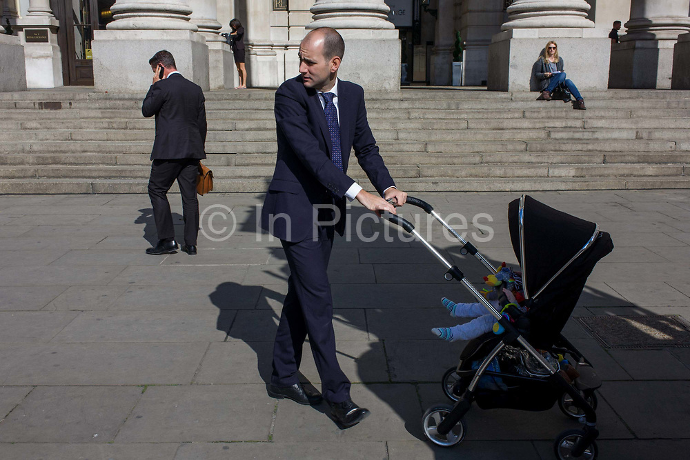 A businessman childminds in the City of London. Circling the area beneath tall pillars of Cornhill Exchange, the man keeps moving to entertain the unseen child. In the background is a young woman who looks on in admiration of paternal instincts. The pavement is in the heart of London's financial districdt, known as the the City of London or Square Mile, founded by the Romans as a trading centre in AD43.