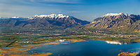 An Aerial Panorama of Provo and Orem cities with Timpanogos and Provo peaks in the background and Provo Bay in the front.