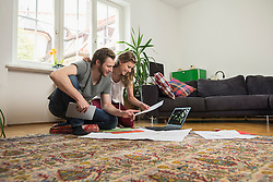 Couple looking at map in living room, Munich, Bavaria, Germany