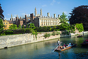 Punts and passengers glide past Clare College founded 1326 on the River Cam past the Garret Hostel bridge, Cambridge, UK.