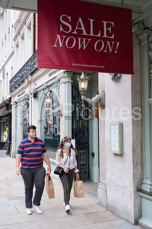 As Britain enters a period of deep recession, with some shops closing either temporarily or permanently as the economic downturn caused by the Covid-19 pandemic cuts hard, shoppers wearing face masks continue to come to the West End while shops massively reduce prices in a wave of sales including Fortnum and Mason on 13th August 2020 in London, United Kingdom. The Office for National Statistics / ONS has announced that gross domestic product / GDP, the widest gauge of economic health, fell by 20.4% in the second quarter of the year, compared with the previous quarter. This is the biggest decline since records began. The result is that Britain has officially entered recession, as the UK economy shrank more than any other major economy during the coronavirus outbreak.
