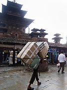 A laborer is carrying a huge load of boxes, traditioal Nepalese style, through Kathmandu in the rain, next to Hanuman-Dhoka Durbar Square.