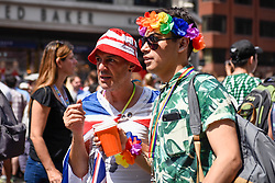 © Licensed to London News Pictures. 07/07/2018. LONDON, UK. An England fan from Camden in town to watch the England v Sweden World Cup football match views the annual Pride in London Parade, the largest celebration of the LGBT+ community in the UK.  Photo credit: Stephen Chung/LNP