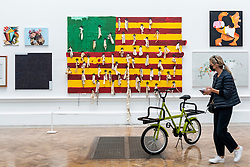 © Licensed to London News Pictures. 15/09/2021. LONDON, UK. A flag entitled OSSEMENTS (ÉTATS  DÉSUNIS' D'AFRIQUE) by Nú Barreto and a bicycle entitled  'DONKY' by Wilson Brothers. Preview of the Summer Exhibition 2021 at the Royal Academy of Arts in Piccadilly. Co-ordinated by Yinka Shonibare RA, the exhibition explores the theme of 'Reclaiming Magic' to celebrate the joy of creating art with around 1400 works by emerging and established artists featured in the exhibition.  The Summer Exhibition is the world's largest open submission contemporary art show and has taken place every year without interruption since 1769.  Photo credit: Stephen Chung/LNP