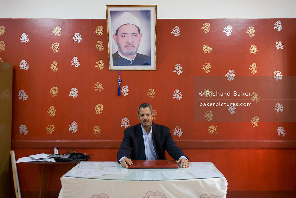 A portrait of the school headmaster beneath a picture of a Muslim cleric at the Islamic Koom al-Bourit Institute for Boys in the village of Qum (Koom), on the West Bank of Luxor, Nile Valley, Egypt.