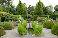 A water feature, hydrangeas, Buxus sempervirens and York stone paving in The Rill Garden at Wollerton Old Hall, Wollerton, Market Drayton, Shropshire, UK