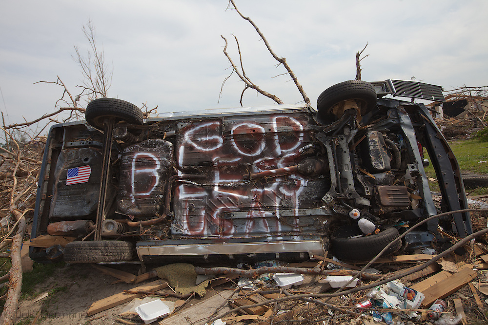 Car thrown by a tornado with an American flag and a blessing pained on it in rubble left in the storms wake. in Pleasant Grove, Alabama. Pleasant Grove, a suburb of Birmingham, remains in a state of ruin over two weeks after it was hit by an F-4 ( possibly an F-5) tornado, one of an estimated 300 that struck Alabama and the neighboring states on April 27th , 2011.