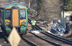 © Licensed to London News Pictures. 17/02/2018. Horsham, UK. A policeman stands on the tracks next to the remains of a car (R) at a level crossing where two people have been killed near the village of Barns Green after a train hit a car. Photo credit: Peter Macdiarmid/LNP