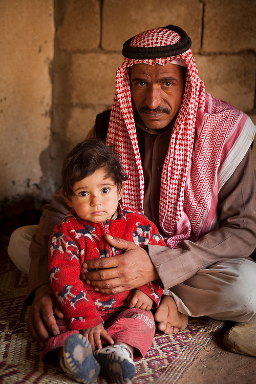 A Bedouin man sits with his baby son at home in Rum Village, Wadi Rum, Jordan.