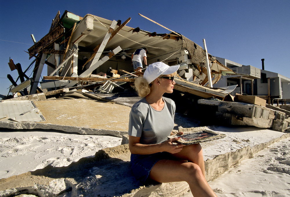 American Barrier Islands: string of dynamic islands reaching from New York, down the Atlantic and across the Gulf of Mexico. Hurricane destruction along islands and coastlline near Destin, Florida.  Woman holds a wedding photo in front of her destroyed home.