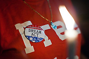 """Sept. 19 - PHOENIX, AZ: A woman wearing a button supporting the DREAM Act at a candlelight vigil at Sen. John McCain's office in Phoenix Sunday. About 30 people met in front of US Sen. John McCain's office in Phoenix Sunday night to demonstrate in support of the DREAM Act, which is scheduled to be debated in the US Senate on Tuesday, Sept 21. The Development, Relief and Education for Alien Minors Act (The """"DREAM Act"""") is a piece of proposed federal legislation in the United States that was introduced in the United States Senate, and the United States House of Representatives on March 26, 2009. This bill would provide certain illegal immigrant students who graduate from US high schools, who are of good moral character, arrived in the U.S. as minors, and have been in the country continuously for at least five years prior to the bill's enactment, the opportunity to earn conditional permanent residency. In the early part of this decade McCain supported legislation similar to the DREAM Act, but his position on immigration has hardened in the last two years and he no longer supports it. The protesters, mostly area students, marched and drilled to show their support for the US military and then held a candle light vigil.   Photo by Jack Kurtz"""
