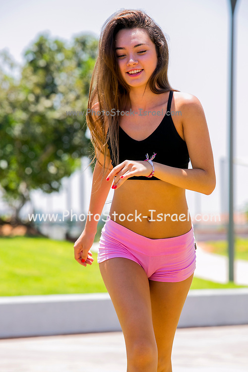 Young teen sportswoman jogging in the park