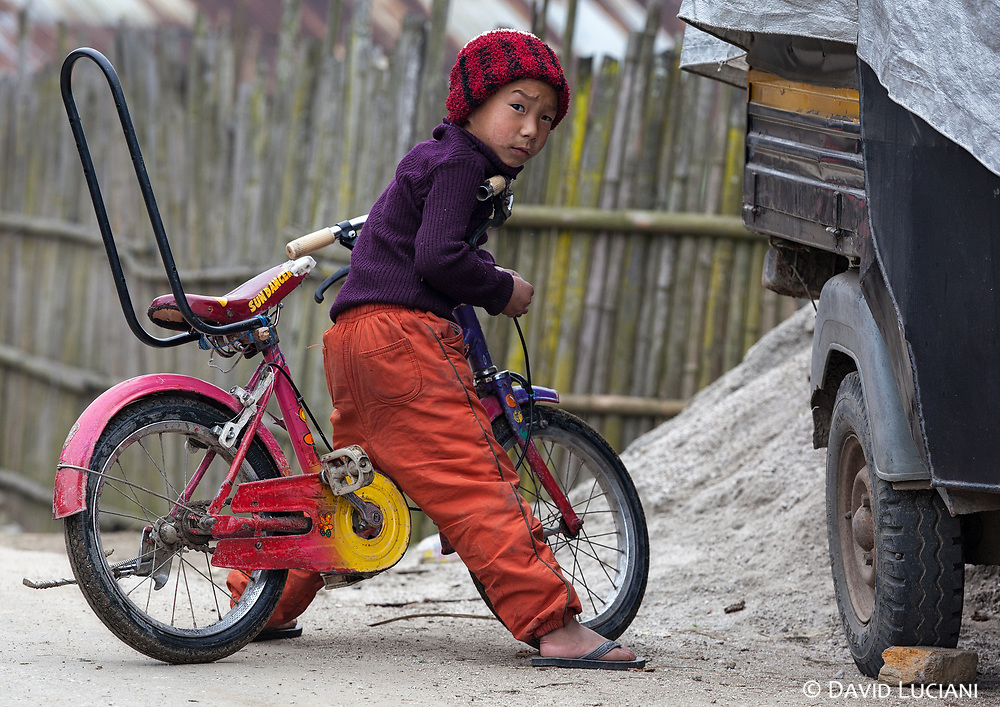 A boy starring at the camera while he is sitting on his cool bicycle in Hari village.