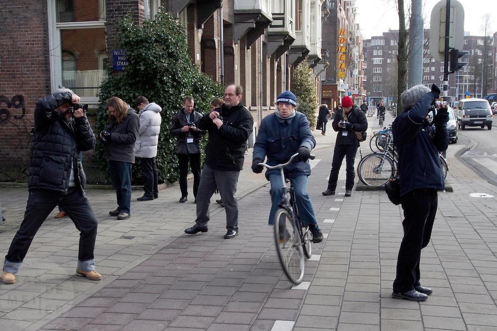 Een fietser ontwijkt fotograferende toeristen die op het fietspad staan.<br /> <br /> A cyclist is trying to avoid photographing tourists in Amsterdam.