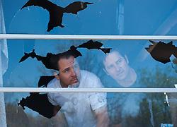 Two men looking out of a broken window