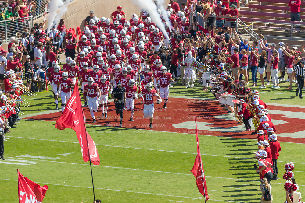 PALO ALTO, CA - OCTOBER 2:  The Stanford Cardinal football team and Head Coach David Shaw (wearing black) enter the field before a Pac-12 football game against the Oregon Ducks on October 2, 2021 at Stanford Stadium in Palo Alto, California; carrying the American flag is Tucker Fisk #88.  (Photo by David Madison/Getty Images)