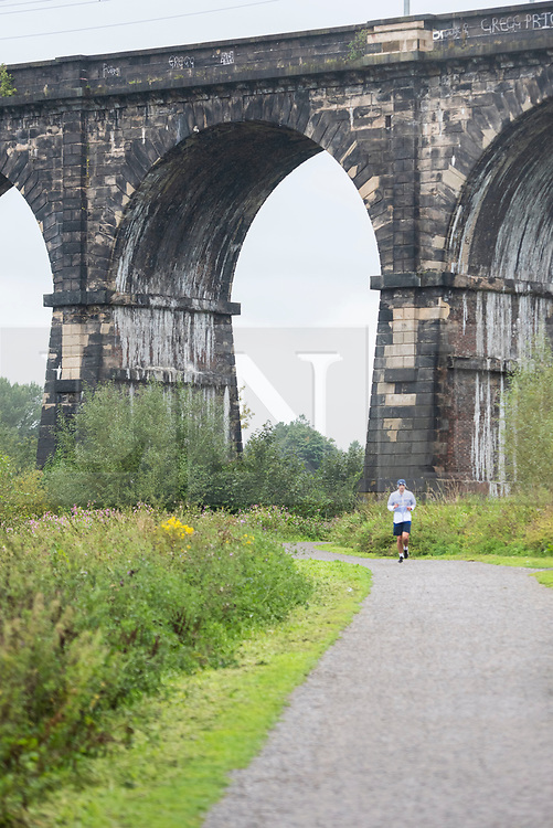 © Licensed to London News Pictures. 28/08/2020. Newton-le-Willows, UK. A jogger runs under the Sankey Viaduct on a wet morning. Photo credit: Kerry Elsworth/LNP