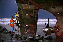 """BLANKENBERGE, BELGIUM - NOVEMBER 9, 2001 -  Workers from the salvage company Unie Van Redding - En Sleepdienst N.V. repair damage to the German cargo ship """"Heinrich Behrmann"""", which was beached by heavy seas after losing power to the main engine late Thursday night at Blankenberge. The ship was heading for the port at Zeebrugge from Ireland, and was carrying dry cargo, none of which was hazardous. Unie Van Redding - En Sleepdienst N.V. was hired to free the ship. Three unsuccessful attempts were made Friday, the second attempt resulted in the injury of two workers when tug boat cables snapped. The beached ship has attracted the attention of curious tourists. (Photo © Jock Fistick)"""