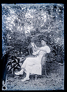 adult woman reading in the garden a French magazine from 1915