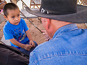 "13 JULY 2012 - FT DEFIANCE, AZ: A Navajo boy talks to a horse wrangler during the horsemanship clinic  at the 23rd annual Navajo Nation Camp Meeting in Ft. Defiance, north of Window Rock, AZ, on the Navajo reservation. Preachers from across the Navajo Nation, and the western US, come to Navajo Nation Camp Meeting to preach an evangelical form of Christianity. Evangelical Christians make up a growing part of the reservation - there are now more than a hundred camp meetings and tent revivals on the reservation every year. The camp meeting in Ft. Defiance draws nearly 200 people each night of its six day run. Many of the attendees convert to evangelical Christianity from traditional Navajo beliefs, Catholicism or Mormonism. ""Camp meetings"" are a form of Protestant Christian religious services originating in Britain and once common in rural parts of the United States. People would travel a great distance to a particular site to camp out, listen to itinerant preachers, and pray. This suited the rural life, before cars and highways were common, because rural areas often lacked traditional churches. PHOTO BY JACK KURTZ"