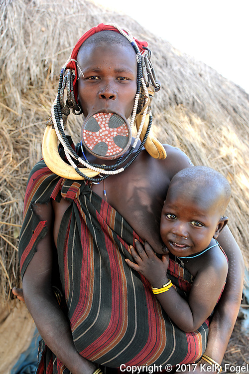 Omo Valley, Ethiopia 2017<br /> Mursi woman holding a baby and wearing a lip plate.  Mago National Park.
