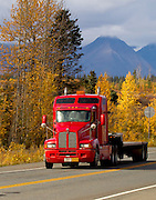 Alaska. Scenic autumn view of a semi-truck traveling south on the Parks Highway through Broad Pass, south of Cantwell.