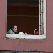 Young woman lost in thought looking out of a window in Burnet's Close, Edinburgh<br />