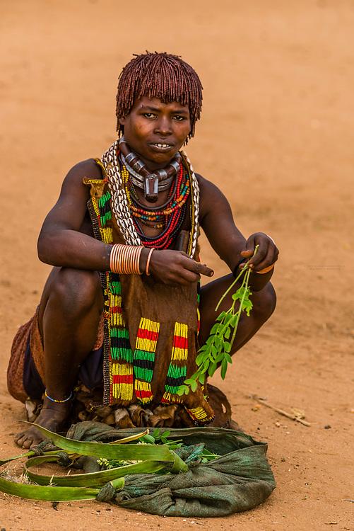 Hamer tribe woman sorting moringa leaves, Omo Valley, Ethiopia.