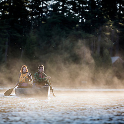 A young couple paddles a canoe through morning mist on Long Pond in Maine's north woods. Near Greenville, Maine.