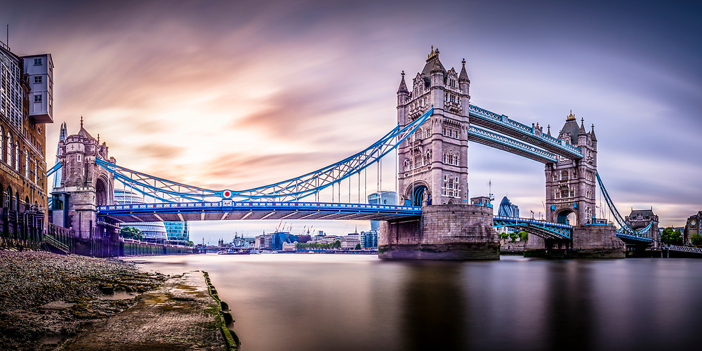 Long exposure panorama of Tower Bridge taken from the Thames River beach at low tide.
