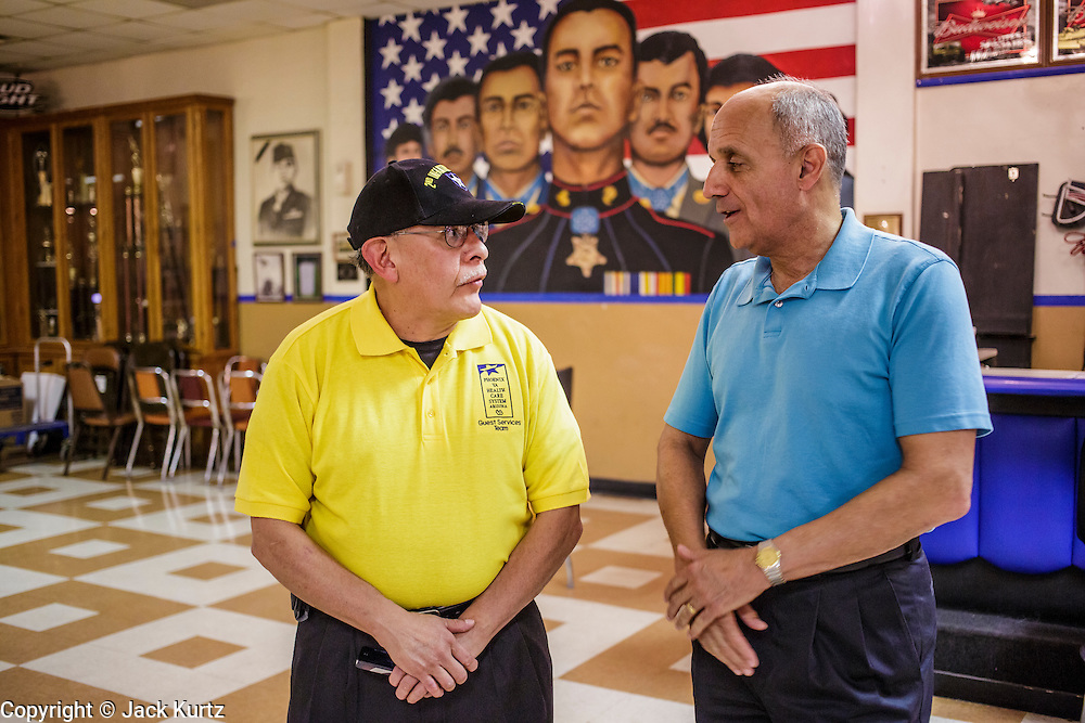 02 AUGUST 2012 - PHOENIX, AZ:   Dr RICHARD CARMONA (blue shirt) talks to a veteran during a campaign stop at an American Legion Hall in Phoenix Thursday. Carmona, the former US Surgeon General under President George W. Bush, is running for the US Senate as a Democrat. Carmona's personal story is an important part of his campaign. He dropped out of high school to join the US Army. He applied for Special Forces and was turned down because he didn't have a high school diploma, he got his GED, reapplied and was accepted into Special Forces. He served in Vietnam as a combat medic. After he was discharged, he went back to college, became a R.N., went to medical school and became a surgeon, became a police officer and member of the SWAT Team in Tucson, AZ. He became the surgeon general in 2002 and returned to Tucson after his term as surgeon general.   PHOTO BY JACK KURTZ