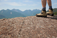 Close-up of hiker's boots standing on a mountaintop
