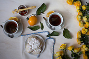 Tea, Scones, Yellow Roses and Lemons on White Wood