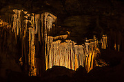 The texture of the main cave in Carlsbad Caverns National Park, New Mexico, shows folds, curtains, terraces and other decorative features. The decorations, known as speleothems, are formed when groundwater containing calcium bicarbonate solution seeps into the cave. Then that solution is exposed to the air in the cave, carbon dioxide gas is released and calcite is deposited.