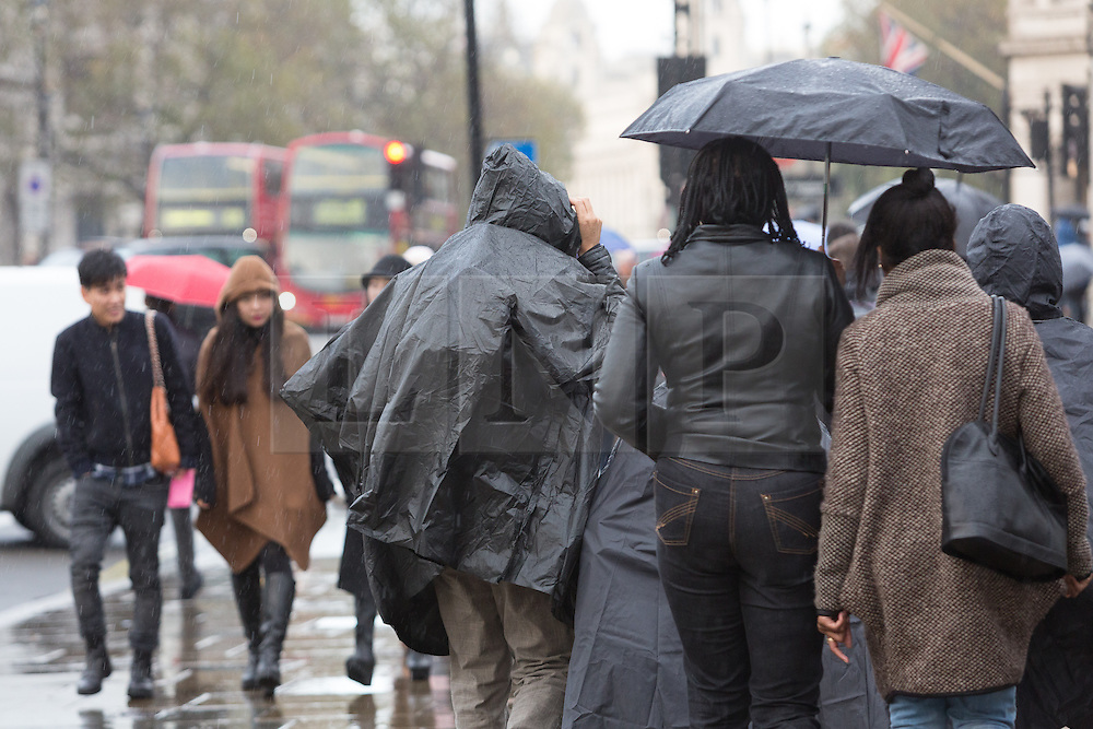 © Licensed to London News Pictures. 10/11/2014. London, UK. People and tourists with umbrellas during rain near Westminster Bridge in central London this afternoon. Photo credit : Vickie Flores/LNP