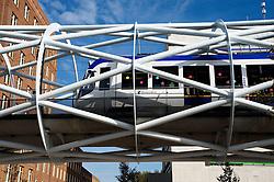 Modern public tram running on modern architectural steel truss bridge in centre of The Hague in The Netherlands