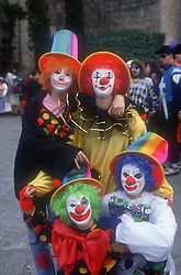 Group of clowns standing in street wearing colourful costumes at carnival in Toledo,