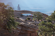 Visitors look through Mesa Arch in Canyonlands National Park, Utah.  Picture by Andrew Tobin.