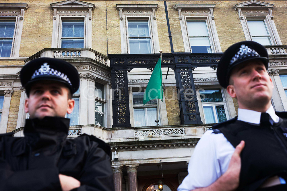 Two police officers guard the outside of the London Libyan embassy that still flies the pro-Gadaffi flag. Seen from a low-angle, we look up top the two men in the uniforms of the Metropolitan police, we focus on the green flag of revolutionary Libyan dictator Muammar al-Gaddafi who made the solid green colours the emblem of his regime. On 1 September 1969, a small group of military officers led by then 27-year-old army officer Muammar al-Gaddafi staged a coup d'état against King Idris, launching the Libyan Revolution. In the days after the uprising sweeping across the north African country, the embassy remains loyal to the beleaguered government.