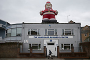 Large inflatable Santa on the roof of an industrial estate building on the Isle fo Dogs, London, UK.