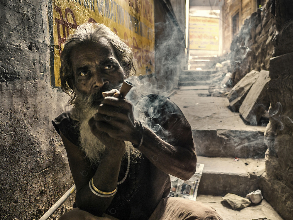 Varanasi, India - October 06, 2015 Indian in ascetic clothes smoking ganga ( cannabis ) in an alley Varanasi India. This city is known to have a high consumption of cannabis specially among saddhus as Varanasi was founded by the ganja-loving deity Lord Shiva.
