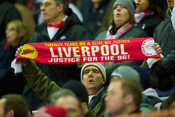 LIVERPOOL, ENGLAND - Wednesday, December 15, 2010: A Liverpool supporter holds aloft a scarf calling for justice for the 96 victims of the Hillsborough stadium disaster, during the UEFA Europa League Group K match against FC Utrecht at Anfield. (Photo by: David Rawcliffe/Propaganda)